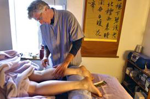 PHOTO: JOSHUA LAWTON Acupuncturist Chris LaRosa removes needles during a leg treatment on Cat Figaro-Reifsteck, of Thornton, for restless leg syndrome in his Boulder office,